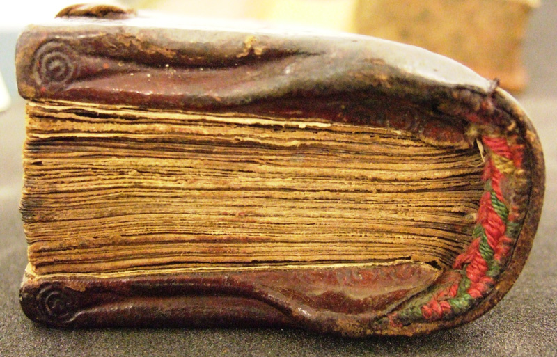 The head-edge of a 13th-century Psalter, showing V-shaped edges of the boards and head end band.