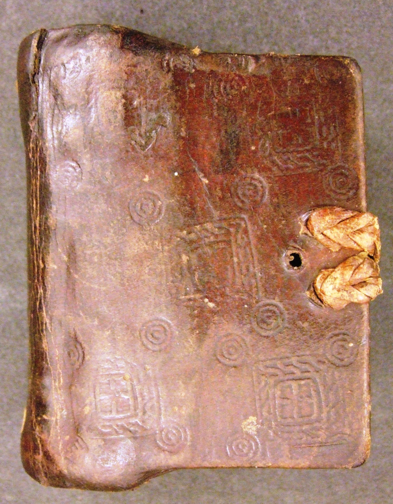 The back-board of a 13th-century Psalter, with lacing of the leather straps with unused hole.