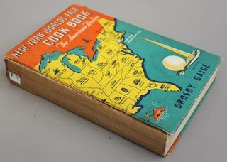 Part one of three images. This image shows a book, lying on a grey surface, titled 'New York World's Fair Cook Book' with a yellow map of the Eastern half of the United States of America in yellow on a blue background. The spine of the book is missing and the spine lining is exposed.