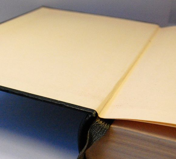 A book bound in green leather with the front board open. The first page, the endpaper, is made from a single folded piece of cream paper, double the size of one of the book's pages, the left hand side of which (the pastedown) is stuck to the inside of the board.