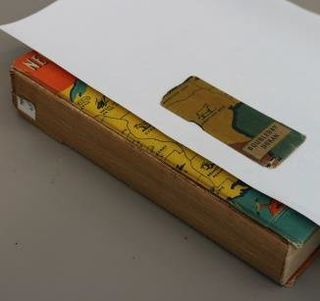 Part two of three images. A close-up image of the World's fair book, with a white piece of blotter paper lying on the cover, while a fragment of the spine is lying on top of .