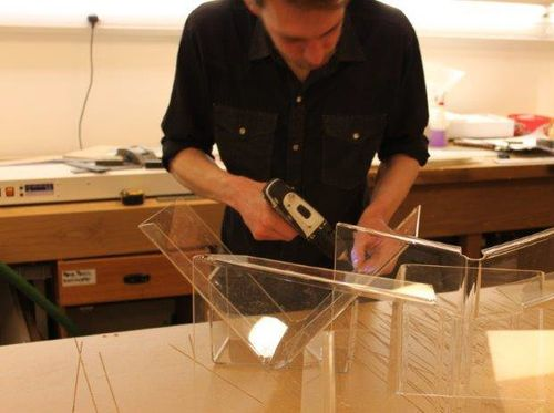 A technician, wearing a blue shirt, is seen in this image wielding a drill, whilst building a perspex book cradle in an exhibitions workshop.
