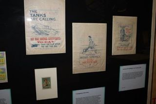 Image one of three: A series of paper bags from the First World War era are shown on display. The cream-coloured bag are without handles, and display as posters, against a dark grey wall; white information placards are underneath.
