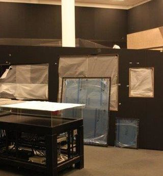 Image two of three: A photo of the exhibition space under construction. There is an empty display case, with a black base and a perspex display top in the foreground, and in the back is the exhibtion wall, with mounted and unmounted items covered in protective wrapping.
