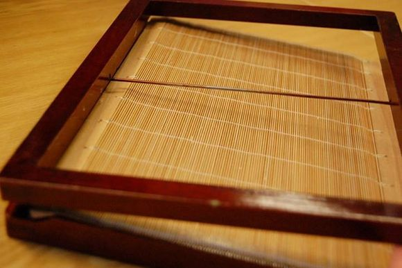 The papermaking screen consists of two dark wood rectangular frames one on top of the other with a screen between them made from parallel strips of bamboo. A thin dark wood dowl bisects the top frame horizontally. The bamboo screen has lines of white stitching crossing it horizontally at regular intervals.