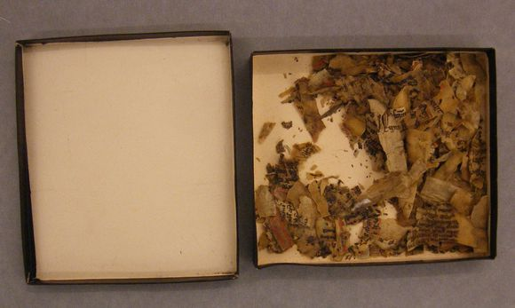 Charred fragments form part of the Burnt Cotton Collection. The image shows a black box with white lining, open with its lid to the side, filled with jumbled fragments. gothic style text can be seen on some fragments.