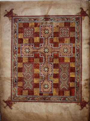 A view of the Carpet page of St Jerome in its entirety. The manuscript page itself has some staining, particularly in the top middle which has run into the image. There is much dirt around the edges, and also close to the binding. The Image itself is central to the page. It consists of a large horizontal rectangle, bordered at the corners with elaborate finials, of hounds with teeth clenched into the corners of the image. The outer border is red, followed by a thick inner decorative border containing intertwined birds in teal and red on a black background. This border is then supplemented by a smaller thinner border of faded blue. Within that is the main image itself, a stylised cross done as squares, on top of a red and gold celtic-style knotwork in small squares.
