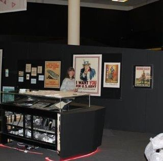 Image three of three: A staff member walks around the exhibition space. Similar to the previous image, the display case to the fore of the image is still empty, though some of the pictures in the background have had their protective wrapping removed.