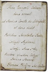 A piece of cream paper pasted inside the back board of the book, covered with ten lines of Latin writing in dark brown ink. The paper is torn and folded in on the edges and at the corners. The number 91 is written in red crayon at the top of the piece of paper, above the first line of writing. The paper has some old dirt ingrained into its surface, which show the contours of the board and folds of the covering leather beneath.