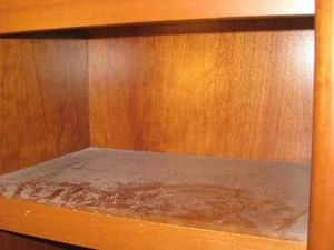 A wooden bookcase, in a warm wood, possibly pine, with a large amount of dust on it shelf. Towards the lip of the shelf the dust has been disturbed by hands and fingers, showing the amount of dust which is on the shelf.