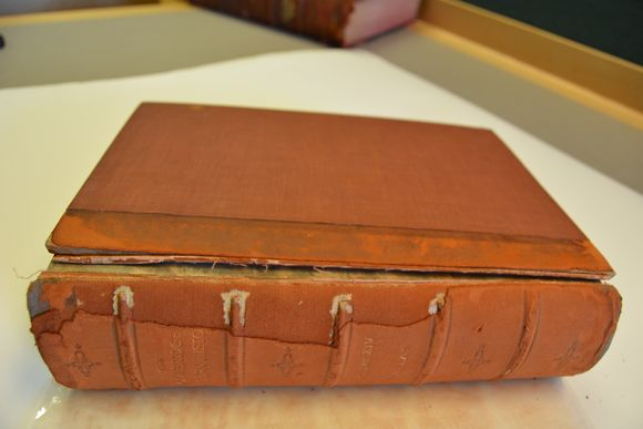 An image of a hardbound book lying on it's side on a white piece of paper, on a grey table. The spine is facing the camera. The front board has detached completely, thoug still sitting on the text block. The spine shows heavy wear on the head and tail, and the leather has worn away from the riht-hand edges of four of the five bands. The entire book is a terracotta colour, indicative of major red rot, and the title and any spine decoration cannot be made out clearly. The white sheet underneath the book shows the red 'dust' shed from the book.