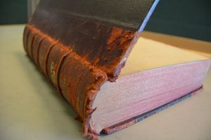 another shot of the same book, this time with the front board opened upwards. the red rot can be seen on the textblock, staining the bottom a pinkish colour.