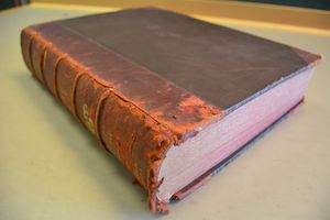 A hardbound flexible tightback book, seen viewed fromthe lower edge of the spine. The book is sitting on a grey table. The red-rot can be seen along the tail and the leather area of the front board which has started to flake away.