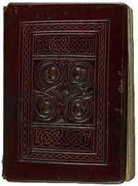 An example of Leather binding on a book. The image is small, but focuses on the frontispiece of a book, which has beautiful celtic knotwork framing a sigil of four intertwined finials. The entire cover is done in a rich browny-reddish leather, with some wearing to the board edge in the middle.