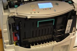 The front of a large office printer with a cover off to show where the CMYK cartridges fit.