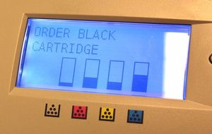 The screen of a standard office printer which shows the levels of ink to indicate when cartridges need replacing. The black cartridge is shown to be low (ink levels displayed as bar graphs) and the message 'ORDER BLACK CARTRIDGES' appears on the screen.