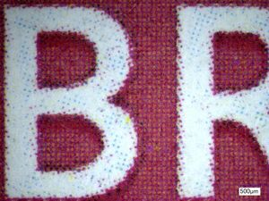 The BR in British is shown here under magnification. You can see a variety of red dots around the white BR, with a few of the CMYK dots visible as well.