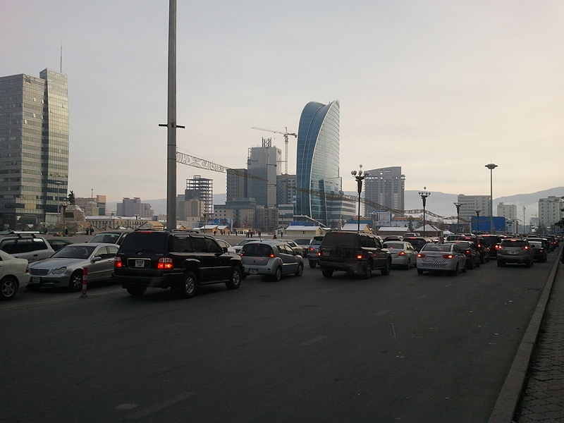 Photograph of lanes of traffic in both directions - totally gridlocked. High rise buildings in the background.