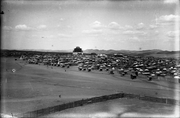 Black and white photograph showing part of Gandan monastery (Megzid Janraiseg)standing out against the gers and single story cabins.