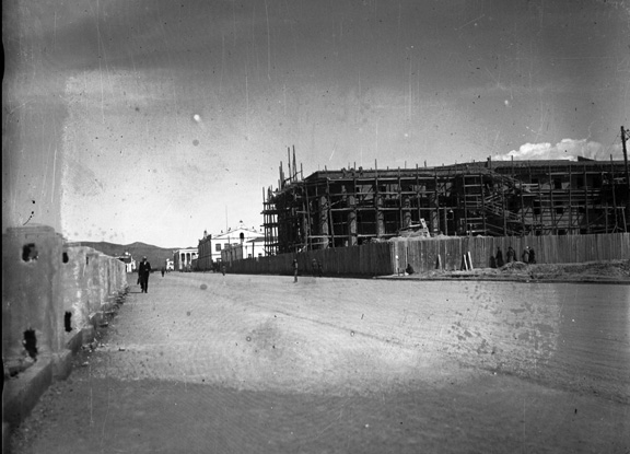 Black and white photograph showing a wide and empty street (apart from a pedestrian). The scaffolding for the opera house is on the right.