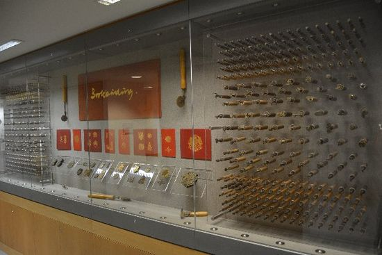 Behind glass sits a variety of gold tools on display alongside examples of the designs created with these tools.