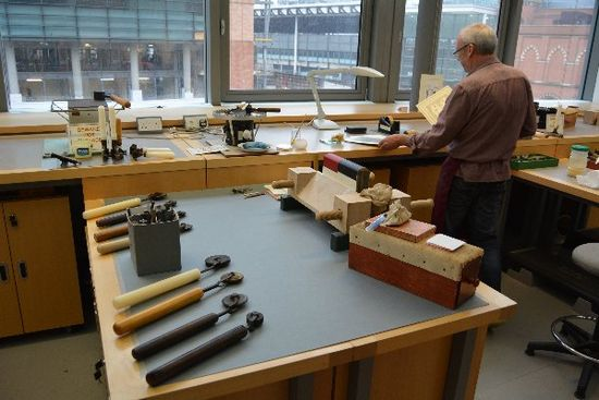On a table in the foreground, a variety of items rest on a table in preparation for gold tooling: a book in a wooden book press, gold leaf, and various metal tools which will be heated and pressed into the book's leather.