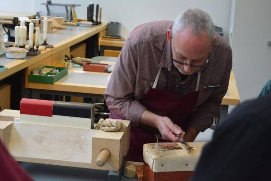 Doug bends over a raised platform which has the gold leaf on it, using a knife to delicately cut the gold leaf. To the left of him is the book in the wooden press.