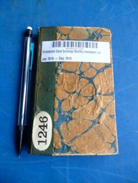 The book sits on a table with a mechanical pencil to the let of it. the book has a marbled covered, mainly in tones of yellows and blues, with a green-blue coloured spine.
