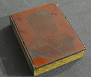 Image shows printing block of Steve Fairbairn, it is a reddish metal plate (consisting of lead tin and some antimony) with a copper electrolytic layer). It is attached with steel screws to a 21mm thick light colour wooden block.