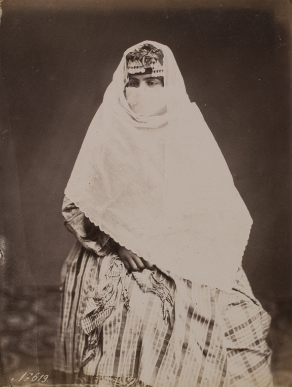 Portait of the same woman. the veil covers her face from the nose downwards. Only her eyes and the cap can be seen.