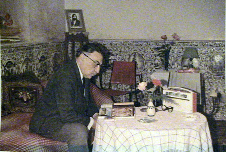 A man sits on a sofa reading a book that is placed on a round table covered in a cloth. A small vase, glasses and a transistor radio are also on the table.