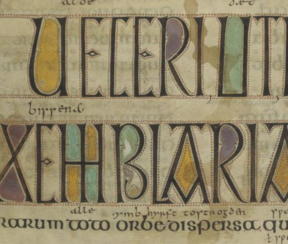 An area of the fourth and fifth lines of text, which are written in black while the enclosed areas inside the letters are filled with blue, purple, green and yellow pigment. There are areas of brown liquid staining on both lines of text.