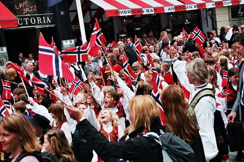 Photograph of a crowd of children in national costume waving Norwegian flags
