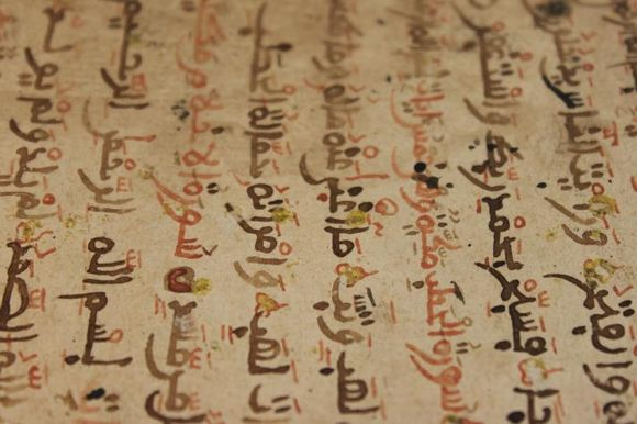A page of the manuscript showing Arabic writing in red and black ink. The picture is sideways, so that the text flows from the bottom to top of the photo. There are yellow dots placed throughout the areas of text.
