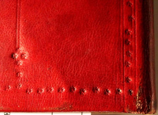 A detail of the decoration of the lower right corner of the back board of a book. It is covered in red leather, onto which the decoration is stamped. The decoration consists of a border of lines and small five-petalled flowers. In the left hand side of the photo is a double vertical line coming down to meet the border. At the bottom of the line, above the border, is a diamond motif consisting of four five-petalled flowers with a single five-petalled flower beneath it.