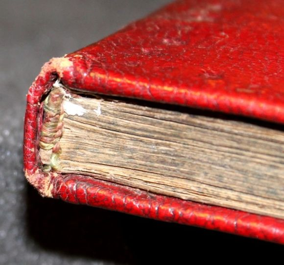 A view from above of the top edge of a red leather-bound book. The leather is cracked and abraded. The endband is made from pink, yellow and green silk threads wrapped around a cylindrical core in a striped pattern.