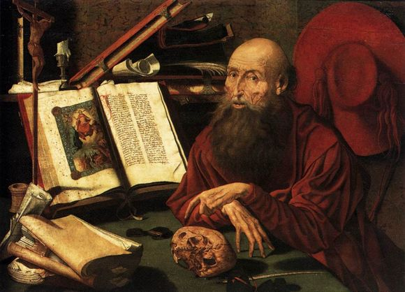 St Jerome sits at his desk with an illuminated manuscript open. In front of him rests a skull. Around him are things like other paperwork, a hat, a candle, etc.