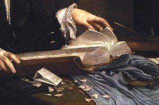 A closeup showing the man flipping through the open book.