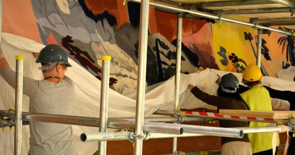 Three people in hard hats stand on scaffolding and re-hang the large tapestry.