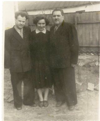 Photograph of the Leokumovich family standing by a fence