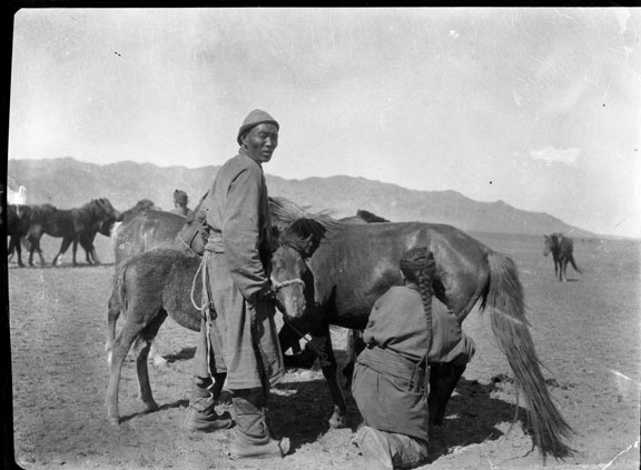 A man holds the foal as his wife milks the mare