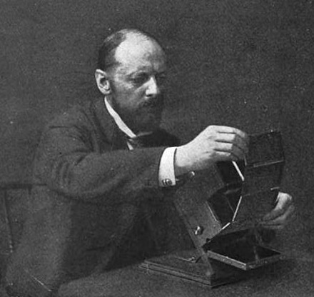 Black and White Image of Frederic Ives, circa 1899. The image shows Eugene inserting Kromogram into his Kromskop which is resting on a table in front of him.
