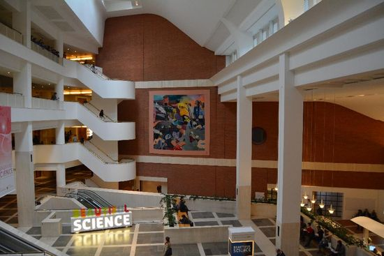 A wide birds eye view of the British Library's large and open foyer with the Kitaj tapestry hanging on the brick wall straight ahead. The tapestry is flanked on either side white architectural features, to the left are open plan levels and winding staircase, to the right are two tall white pillars which merge into the upper mezzanine.