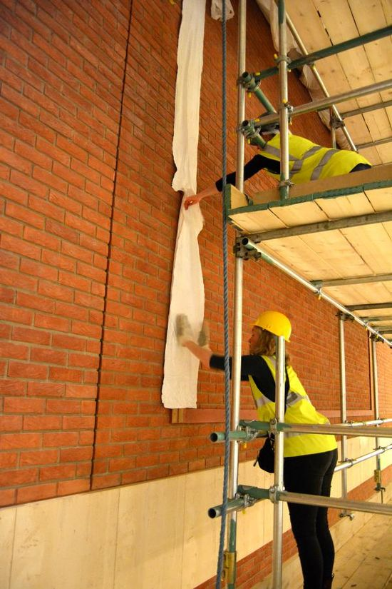 Close up of two conservators in yellow high vis. vests standing on scaffolding by the red brick wall, one conservator is standing on a level of scaffolding above the other. They both have their hands extending outwards towards the wall, where they work together to apply a protective material on top of the Velcro battens before the tapestry is lowered. This will allow a safe and controlled lowering and attachment of the tapestry.