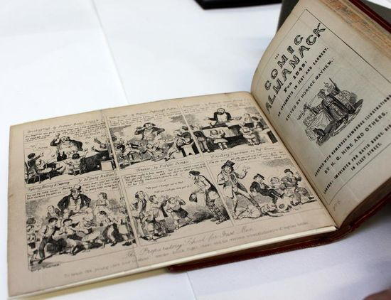A close up of an opened book on a white table. The opening is of a black and white early 20th century comic. The left page is originally double the length and vertically folded in half. In this image the left page has been opened up to show the full comic, with a piece of mount board below to support the full length of the page opening.