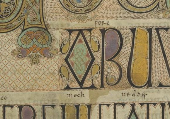A close-up of the right side of the initial showing decorative animal heads which are purple with yellow noses and orange bodies. Sections of black text from the second and third rows are also shown. The black letters of the second row have areas filled in with purple and yellow pigment and are decorated with intertwining bird heads and necks. Around the initial decorative red dots are arranged in a diamond pattern; around the black letters red dots are arranged in straight lines.