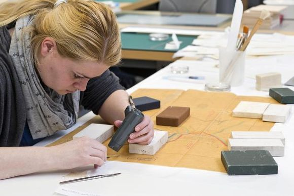 Kim has long blonde hair tied in a ponytail, and is wearing a grey scarf and cardingan. She is on the left side of the photo, sitting in at her workbench with her right side facing us. On her bench in front of her is a orange-brown map made of tracing paper, with red and black lines drawn on it. The map is weighted down with square weights covered in white, black and brown fabric. Kim is leaning over the bottom right corner of the map, which she is treating with a small black hairdryer held in her left hand. A metal scalpel lies on the bench next to her right hand.
