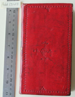 The front board of a book bound in red leather. The leather is creased and scratched and the corners of the board have been bashed with use and small areas of the leather are missing from them. The book is much narrower than it is tall.The board is decorated with a border of lines and small five-petalled flowers. There is a double vertical line down the centre of the board. In the centre of the board a diamond shape has been created from five-petalled flowers, with further small diamonds positioned on each of the four points.
