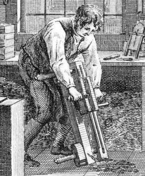 A closeup of one of the workers who is using a tool that resembles a wooden vice with a sharp blade attached. A textblock rests in the vice and the blade is dragged over the edges of the textblock to shave them down to a uniform size.