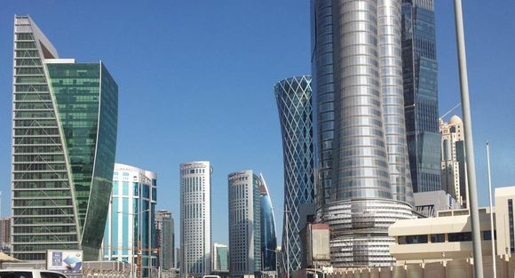A partial skyline of Doha with skyscrapers dotting a bright blue sky. The buildings are all very modern featuring metal, glass and lots of curves.